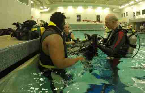 Learning to dive SCUBA pool session gearing up.